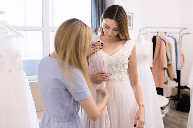 若い女性の裁縫師は女性に合ったドレスを作る
