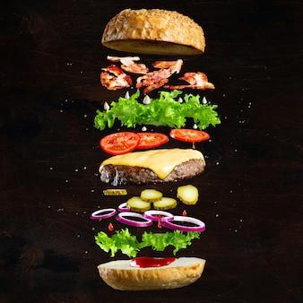 Ингредиенты вкусного гамбургера с котлетой из говяжьего фарша, листьями салата, беконом, луком, помидорами и огурцами
