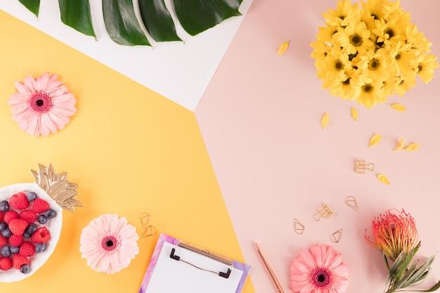 ノートパソコン、花、明るい黄色とピンクの背景に緑のヤシの葉を持つ女性ビジネス職場。夏の時間で女性の作業スペースの平面図。平干し