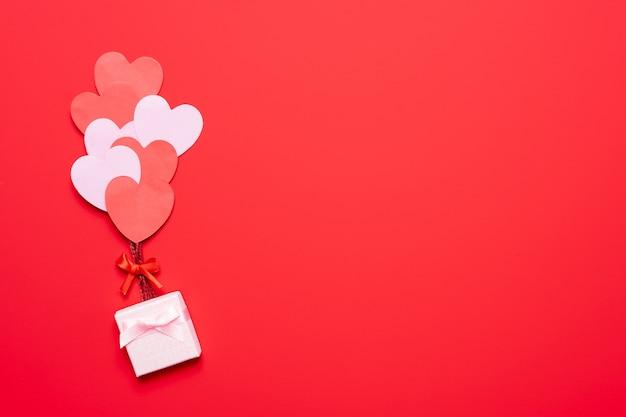 ピンクの背景の風船のような赤とピンクのハートとバレンタインデーの背景、フラットレイアウト
