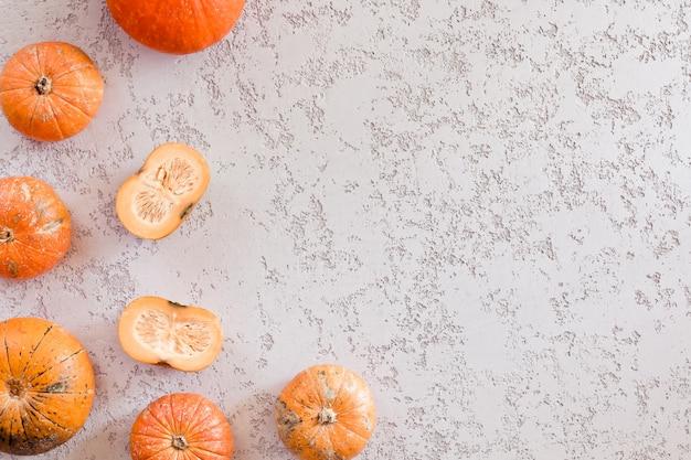 Разные тыквы на белом фоне стола, вид сверху