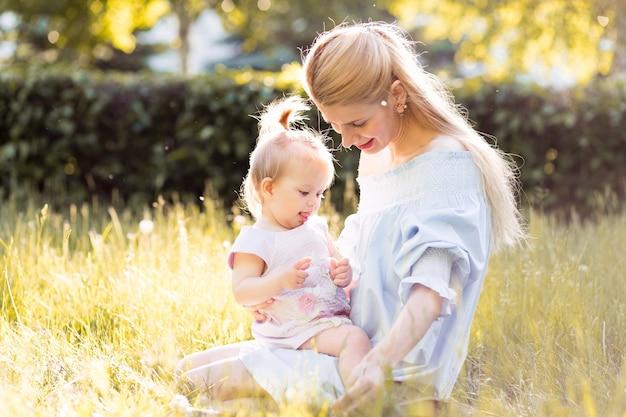彼女の女の赤ちゃんを持つ若い美しいブロンドの母親