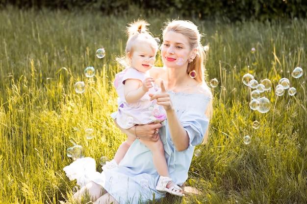 小さなかわいい赤ちゃんの娘と幸せな若い母親の肖像画