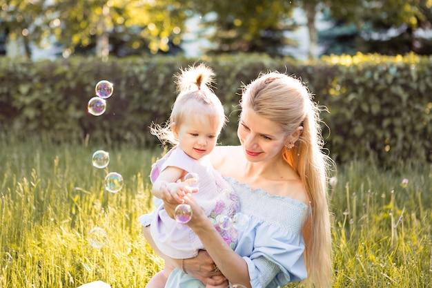 母と春の日に屋外のシャボン玉を吹く小さな赤ん坊の娘