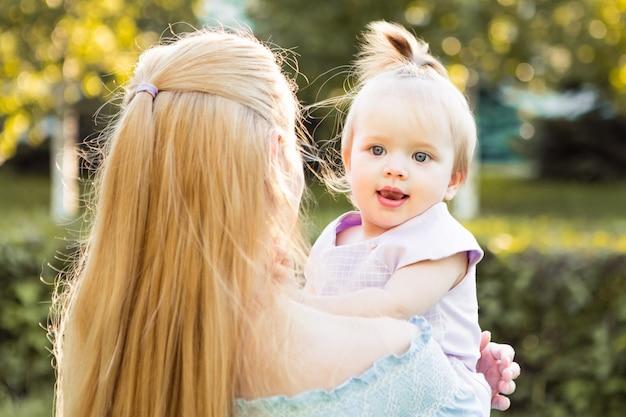 一緒に時間を過ごす小さなかわいい赤ちゃんの娘と幸せな若い母親の肖像画