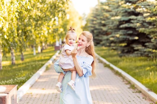 一緒に笑っている彼女の女の赤ちゃんを持つ若い美しいブロンドの母親