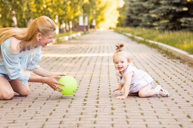 夏の公園で小さなかわいい赤ちゃんと幸せな若い母