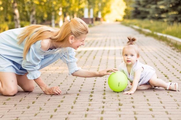 夏に一緒に時間を過ごす小さなかわいい赤ちゃんと幸せな若い母親
