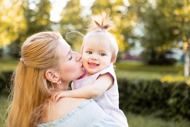 夏の公園で小さなかわいい赤ちゃん娘と幸せな若い母親の肖像画