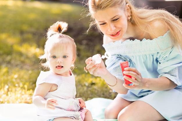 母とシャボン玉を吹く小さな赤ん坊の娘