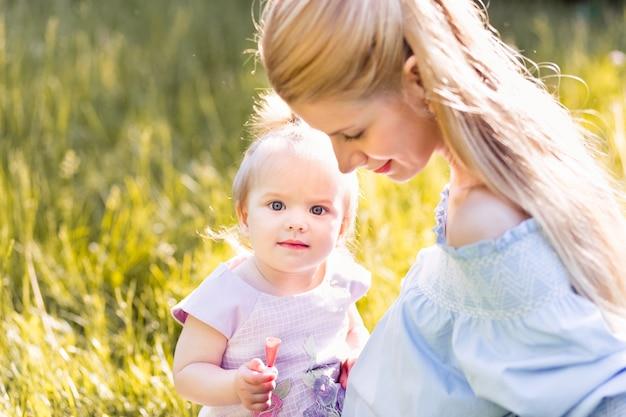 日当たりの良い夏の日に彼女の女の赤ちゃんを持つ若い幸せな母