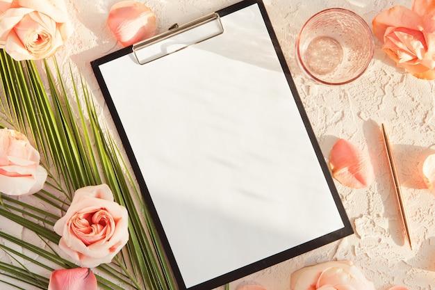 空白の画面のタブレット、熱帯の葉、影と日光と白のピンクのバラの花を持つオフィス女性デスクのトップビュー