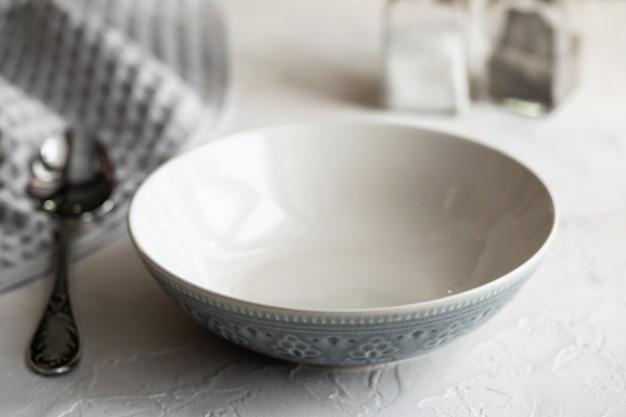 Одна бело-серая миска для супа и ложки на белом столе