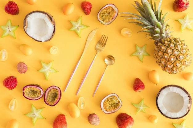 Ананасы, кокосы, ягоды на пастельно-желтых