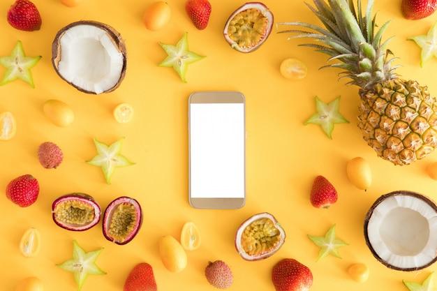 Экзотические тропические фрукты с мобильным телефоном