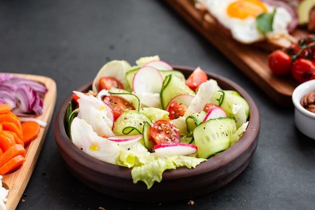 レタス、トマト、キュウリ、タマネギ、ゴマのヘルシーなクラシック野菜の新鮮なサラダ、ブラックプレートとグレーのオリーブオイルドレッシング。