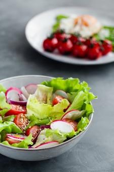 レタス、トマト、キュウリ、タマネギ、ゴマのヘルシーなクラシック野菜のフレッシュサラダ、白いプレートと白のオリーブオイルドレッシング。