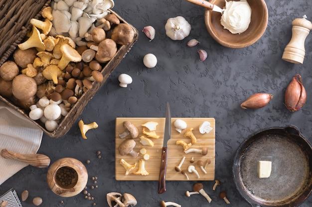 食用の野生キノコの準備と揚げ物、食べ物の写真の平面図。アンズタケ、ポートベロー、しいたけを鋳鉄の鍋に混ぜたもの。スパイス、バター、パセリ、タマネギ、ネギ、ニンニクを使った料理。