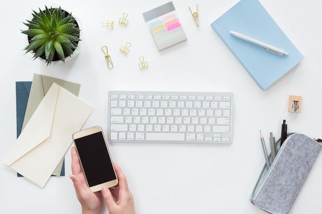 携帯電話で女性の手の上からの眺め、コンピューターのキーボードでビジネス職場、ノートブックフラットレイアウト。