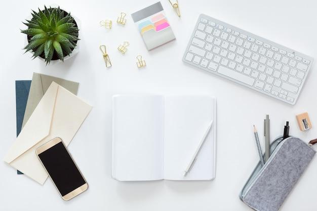 コンピューターのキーボード、ノートブック、緑の鉢植えの花、携帯電話、フラットレイアウトとビジネス職場の上からの眺め。