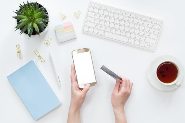 クレジットカードを保持している女性の手の平面図は、ラップトップコンピューターでオンライン支払いをフラットに置く