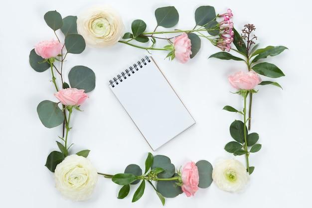 Вид сверху и плоская планировка с блокнотом и рамкой из цветов