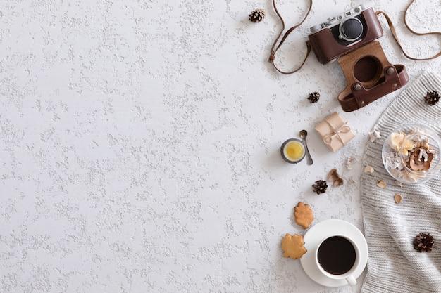 Старинная плоская планировка, вид сверху. ретро камера, цветы и вязаная одежда на офисном столе гипсового стола, копируют пространство. осенний фон