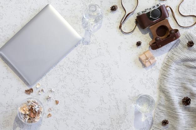 Вид сверху рабочего пространства или офисного стола с ноутбуком, старинный фотоаппарат, одеяло, чашка кофе, имбирное печенье, конус на текстурированном белом фоне