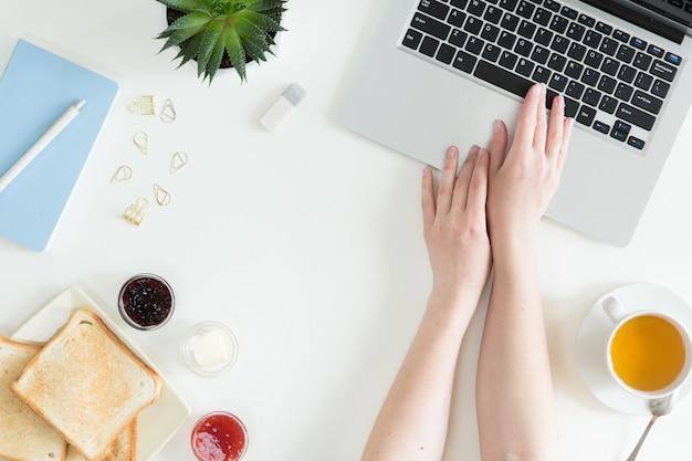 白いデスクトップテーブルの上のノートパソコン、新鮮なサンドイッチ、緑茶、携帯電話のオーバーヘッドビュー。女性ビジネスと朝食のコンセプト、トップビューとフラットレイアウト