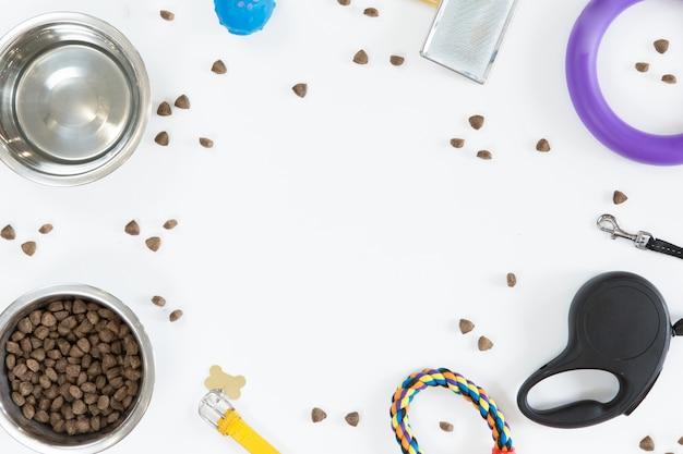 白い背景の上のペット犬のおもちゃやアクセサリー。ドッグフード、リーシュ、首輪、ボールとボウル、平干し、コピースペースの平面図