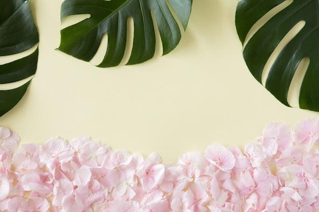 熱帯のヤシの葉とパステルピンクの花で作られた創造的なレイアウトと背景。黄色の背景に夏のコンセプト。フラット横たわっていた、トップビュー、コピースペース。