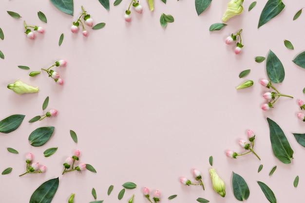 ピンクの背景に分離された葉とコピースペースを持つ丸い花のフレームの平面図を置く。グリーティングカードの概念