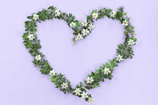 ライラックの背景に野生の花、芽、葉で作られた花ハートフレームの平面図です。コンセプト、フラットレイアウトが大好きです。