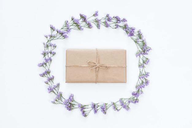 ライトデスクに花のフレームとビンテージクラフトギフトボックスの平面図を置く。休日のグリーティングカード