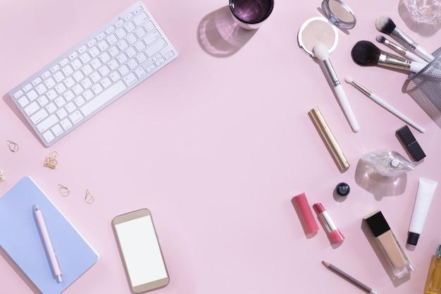 女性の手で白い空白コピースペース画面と携帯電話のモックアップの平面図です。ノートパソコン、装飾的な化粧品セット、文房具と花、ハードライトとフラットレイアウト女性ワークスペース