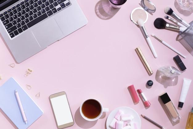 一杯の紅茶やコーヒー、ラップトップやコンピューター、女性がピンクの背景、上からの眺めで製品を作るとフラットを置きます。