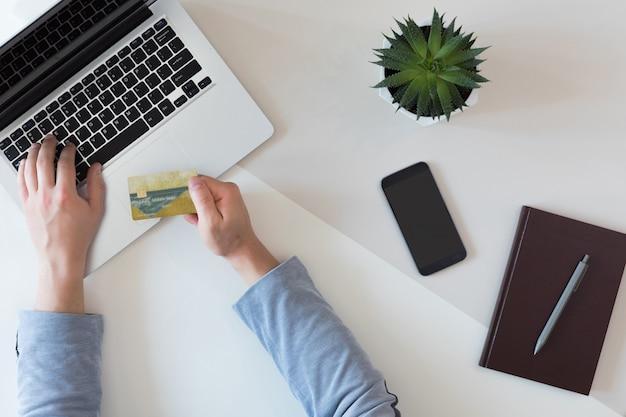 ラップトップコンピューターや携帯電話、フラットレイアウトのオンライン支払いのためのクレジットカードとファッションオフィスデスクのトップビュー