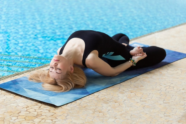 Красивая привлекательная женщина практики йоги ставят на бассейн по утрам, отдыхают в праздничные или выходные дни.