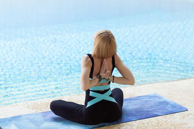 美しい魅力的な女性は、午前中にプールでヨガのポーズを練習し、休日や休日にリラックスします。