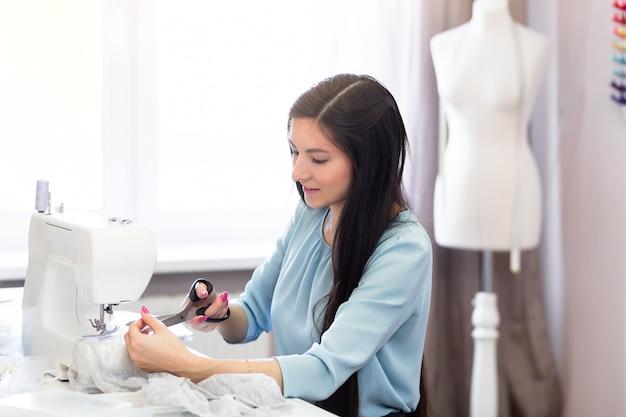 ワークショップ、日光の背景を持つ中小企業コンセプトで笑顔の女性の裁縫師をクローズアップ