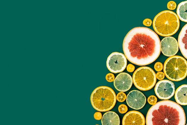緑の背景に明るい柑橘系の果物、夏フラットレイアウトコンセプト。