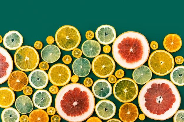 柑橘系の果物とジューシーな新鮮な明るい夏の緑の背景、フラットレイアウト。