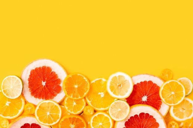 黄色の背景に明るい色とりどりの柑橘類、夏フラットレイアウトコンセプト。