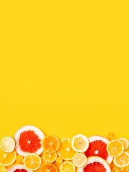 黄色の背景に明るい柑橘系の果物、夏フラットレイアウトコンセプト。