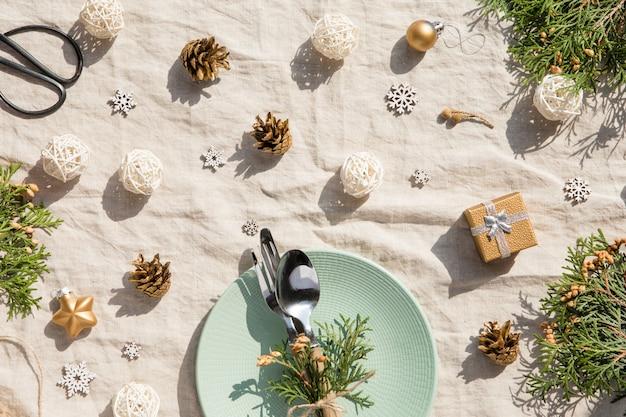 クリスマステーブルの設定。ビンテージのテーブルクロスにプレートとカトラリー、金の装飾、松ぼっくりのクリスマスの休日の装飾