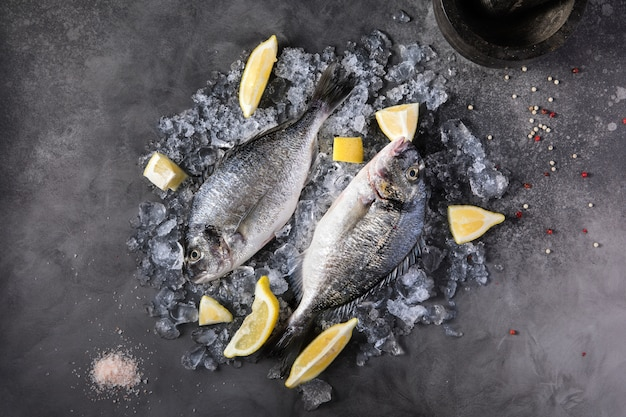 Свежая сырая рыба дорадо со специями, лимон, перец, петрушка
