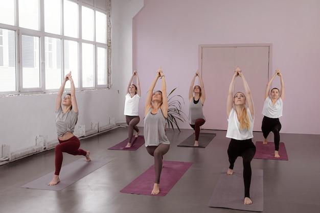 Группа людей делает позу воина йоги в тренажерном зале