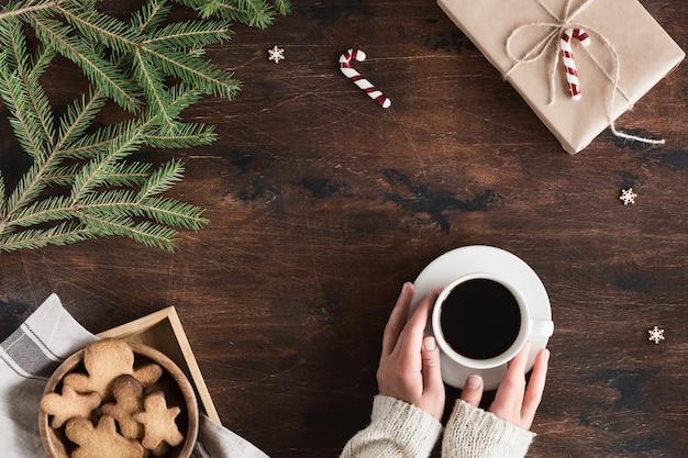 クリスマスのモミの木の枝、ジンジャーブレッドマン、コーヒーカップ、木製の背景上のコンピューター