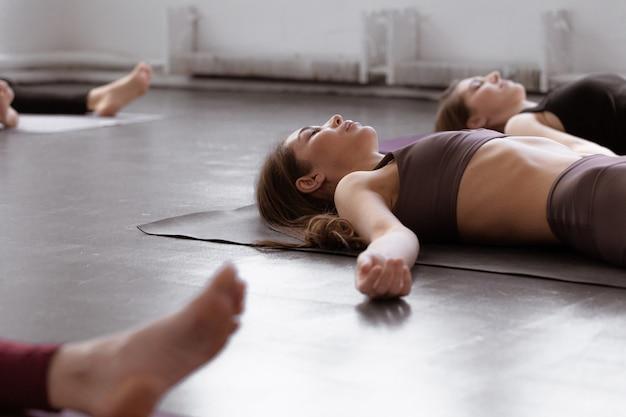 Группа молодых женщин, сидя и медитации в позе релаксации