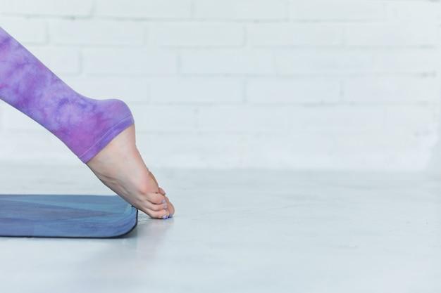 ヨガをやっている女性のスポーツレギンスの足のクローズアップ